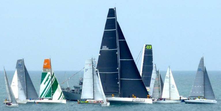 George David's mighty Rambler 88 somehow finds a way through a motley yet representative group at the Naval vessel at the start of the Round Ireland 2016. Included are Class 40s, the J/109 and class winner Euro Carparks (on port), multiple winner Cavatina and Eric de Turkheim' Teasing Machine from France, while beyond is an MOD 70 waiting for the Multi-hull start