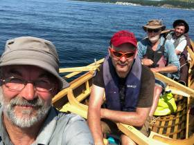 Naomhóg crew Liam Holden (grey cap), Eamonn Ó Muircheartaigh (red cap), Breanndán Ó Beaglaoich and Sean Mac an tSíthigh during their row and sail across Cape Breton in Nova Scotia