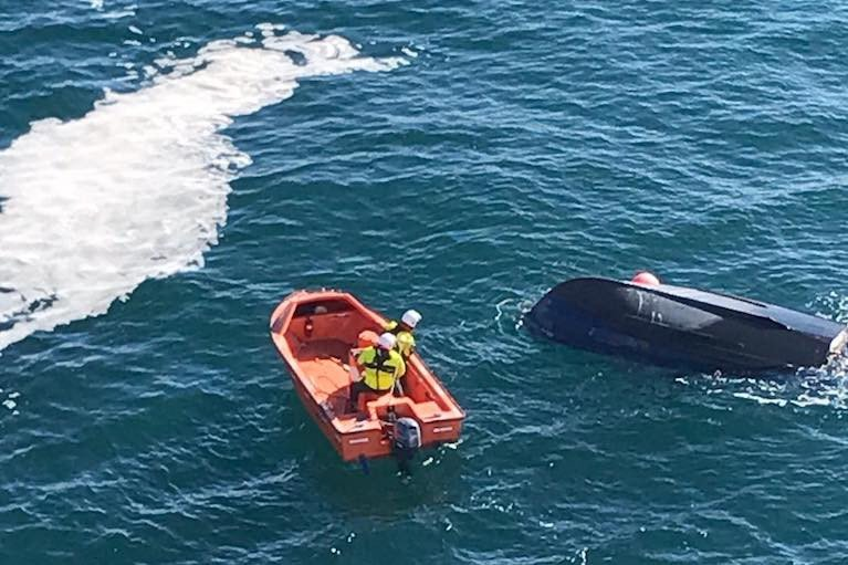 The upturned fishing boat is inspected by the Irish Ferries Isle of Inishmore rescue boat