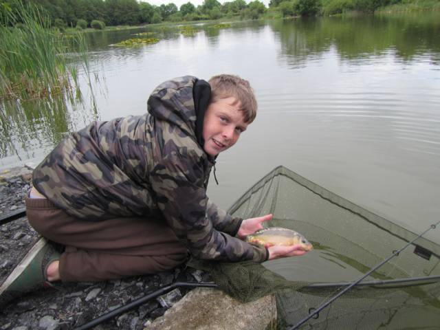 Jamie Powell from Sphere 17 Youthgroup in Darndale, Dublin,  returns a fish to water during a fishing expedition to Gaulmoylestown, Westmeath in June