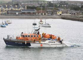Wicklow RNLI's all-weather lifeboat with the dismasted yacht at Wicklow Harbour