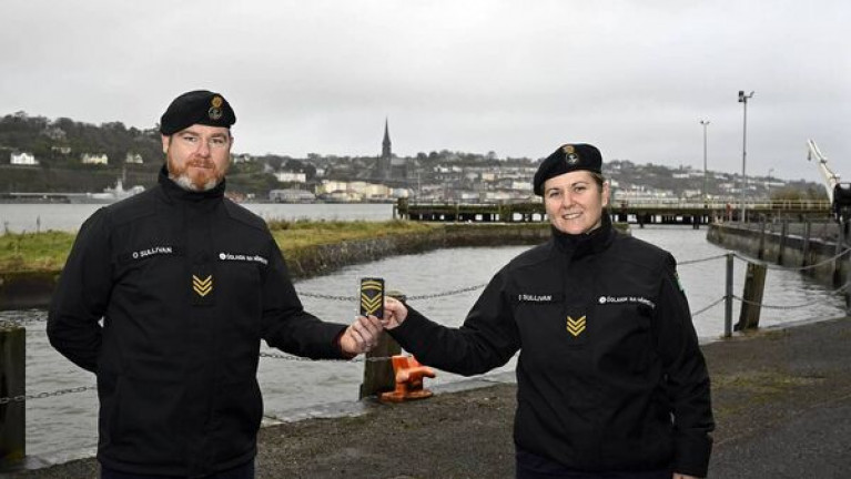 Chief petty officer Patricia O'Sullivan with her new rank markings, alongside fellow petty officer, and brother, Donal O'Sullivan. Afloat adds the photo was taken at the Naval Service Basin in lower Cork Harbour with in the background an Offshore Patrol Vessel (OPV) berthed at Cobh.