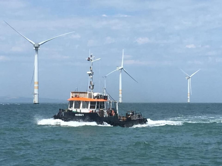 Tug Husky at the Arklow Bank Wind-Farm off Co. Wicklow on the east coast of Ireland, the country's first such facility opened in 2004 is through SSE Renewables' to be expanded. AFLOAT also adds is the tug's fleetmate AMS Retriever which is currently at work on a dredging project at Kilmore Quay, Co. Wexford (see Coastal Notes).