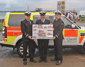 James Larkin (centre) presented with a canvas by new Greenore Coast Guard OIC George Campbell and deputy OIC Shay Gormley
