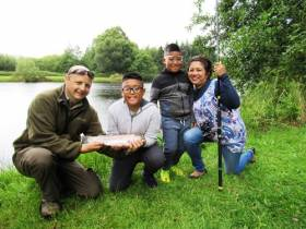 Oisin Cahill of the Dublin Angling Initiative with Darcy Davila Santos (10), his brother Darren (8) and their mother Doreen at Annamoe Fisheries in Co Wicklow last summer. Darcy, a pupil of Rathdrum National School, landed a 4lb rainbow trout to win the Sean McMorrow Memorial Trophy