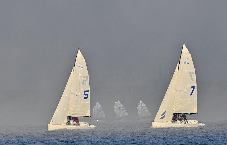 Two Elliott Six Metre keelboat in the foreground and Optimist dinghies sailing in the mist at Dun Laoghaire Harbour