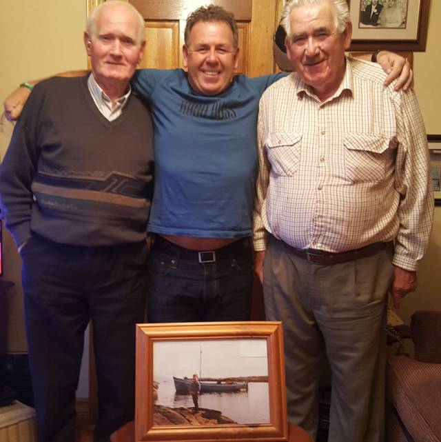 (from left) Michael, Jim and James Gallagher at home in Burtonport, Co Donegal with a photo of half-decker Irine which helped to rescue 15 people, mainly young children, off Roaninish in August 1956