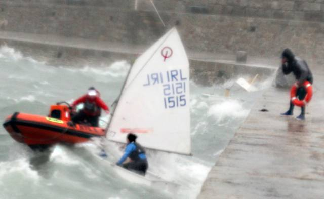 A RIB attempts a rescue of an Optimist Team Dinghy in Dun Laoghaire Harbour during Storm Brian on Saturday. A person on the pier holds a lifebuoy. Two capsized Optimists are just visible in the top right of the picture