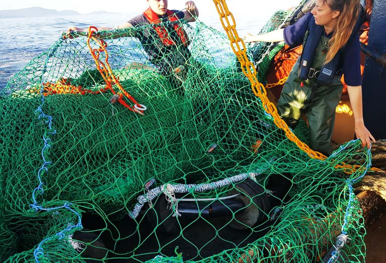 Authors of the study hold up the square mesh panel, inserted into the otter-trawl net with LEDs attached. Lights help to increase escapement of fish through the large square mesh in the panel