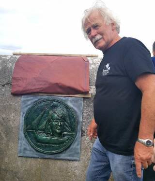 Dr Michael Brogan, Cruinniu organiser, with  the plaque of late Cruinniu founder Tony Moylan designed by John Coll and erected at Kinvara pier.