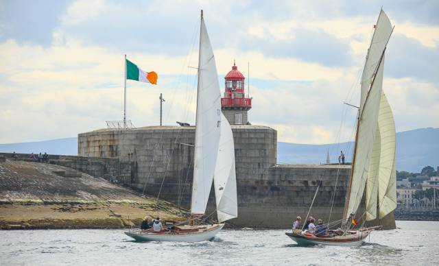 The photo that says a thousand words. Periwinkle and Myfanwy approach Dun Laoghaire harbour towards the finish of the first race on the Kingstown 200 series. To celebrate the 200th Anniversary of Kingstown Harbour, this year's Volvo Dun Laoghaire Regatta 2017 includes a significant fleet of Classic and Traditional vessels, racing for the Kingstown 200 Trophy. And the fleet is varied in the extreme.  Towards the end of their first race on Thursday - which concluded with an in-harbour finish close off the National YC where the classics are berthed - the leader on the water as expected was the superbly-restored Dublin Bay 24 Periwinkle (David Espey & Chris Craig), an Alfred Mylne design of late 1930s vintage.  But the final leg to the harbour mouth was a long reach in a pleasant sou'easter from the middle of Dublin Bay, and the Welsh visitor Myfanwy, a 36ft cutter designed by Alexander Richardson of Liverpool in 1897 (he also designed John Jameson's legendary Irex in 1884) was going like a train. Owner Rob Mason recently restored her himself from virtual dereliction. He has given her a fine suit of sails to match her generous spread of canvas, and with a keen crew, Myfanwy was very much a contender, though Periwinkle did stave her off at the very end.  However, it has given us what could well be the photo that symbolises the Kingstown 200 within Volvo Dun Laoghaire Regatta 200. The splendid granite East Pier now looks as though it is a natural part of the environment – you could well imagine it in place when Dublin Bay itself was formed. The crisp, clean and generously-sized tricolour flying proudly tells us there has been a change of management, but one that increasingly respects all that we have inherited from the past. And coming in past the pierhead are two handsome yachts which speak eloquently of our rich sailing history and heritage, as the Dublin Bay 24s were a major and very successful class in the bay from 1947 to 2004, while Myfanwy is a direct link back to a period when John Jameson of Dublin Bay with his mighty Irex was the most successful yacht owner of his era. Photo: David O'Brien/Afloat.ie
