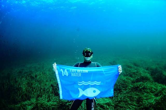 Free diving world champion Umberto Pelizzari raises a flag below water to highlight the plight of life below water
