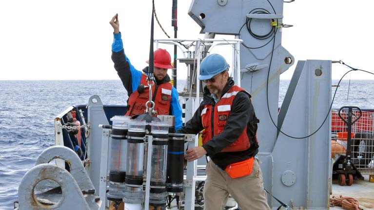 Marine chemist Ken Buesseler (right) deploys a sediment trap from the research vessel Roger Revelle during a 2018 expedition in the Gulf of Alaska. Buesseler's research focuses on how carbon moves through the ocean. Buesseler and co-authors of a new study found that the ocean's biological carbon pump may be twice as efficient as previously estimated, with implications for future climate assessments.