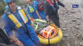 Coastguard rescue team members stretcher the injured cyclist to the lifeboat