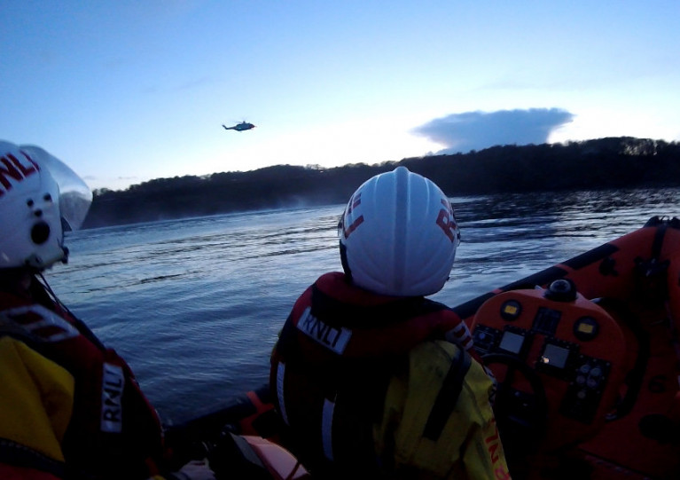 Skerries RNLI volunteers watch as Rescue 116 prepares to winch the casualties