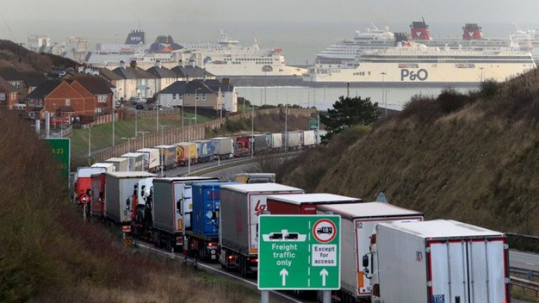 "Trucks queue for the Port of Dover: Irish lorries have been caught up in road-side ""stacking"" of vehicles over the past week. AFLOAT adds ferry operators identified (L-R) DFDS, P&O and a laid-up cruiseship Disney Magic (red funnels) of Disney Cruise Line berthed at the English south-east port in Kent. As Afloat reported last month, DFDS is to launch on 2 January 2021 a new direct freight-only route Rosslare Europort-Dunkirk to bypass post-Brexit congestion, customs checks and clearance. The Danish operator already runs a route from the north French port to Dover but with motorist passengers also included."
