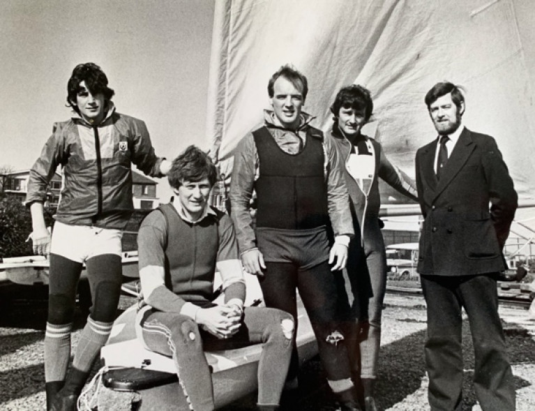 """Warriors About to Go into Battle"". This properly serious-looking foursome from the cream of the 1982 Irish Laser Class, with their mentor Ron Huthcieson on right, are (left to right) Simon Brien (later multiple Edinburgh Cup winner and other majors), multiple champion Charlie Taylor (still at it in the Laser Masters), Olympian Bill O'Hara, and Dave Cummins, All-Ireland Helmsmans Champion 1981 and 1982"