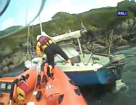 A Union Hall lifeboat volunteer boards the wayward yacht to establish a tow