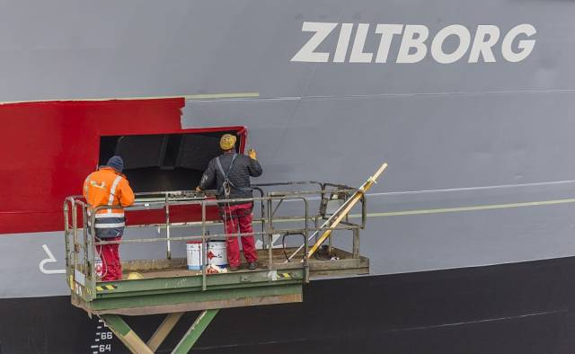 Bow of Ziltborg as employees of a Dutch shipyard apply company colours of Wagenborg, the new Dutch owners of the cargoship which is managed by Corrib Shipping Group based in Dublin