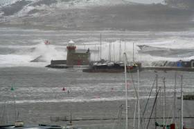 Crazy. Howth Sound at Friday lunchtime, with the East Pier battered at high water at the height of Storm Emma, and the roof of the shed on right sheltering the seven historic Howth 17s beginning to cave in under those monster breakers