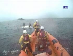 Lough Ree's inshore lifeboat approaches the upturned Fireball and its two sailors