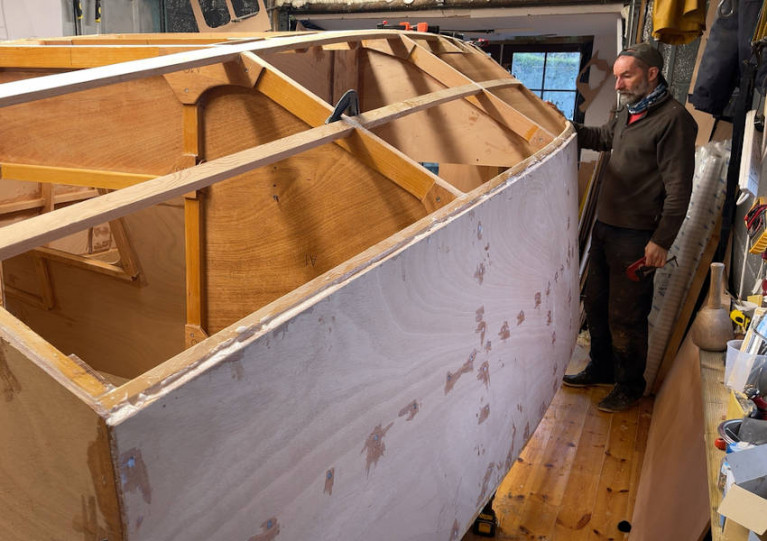 Jim Schofield with the plywood-and-epoxy hull of his ClassGlobe 5.80