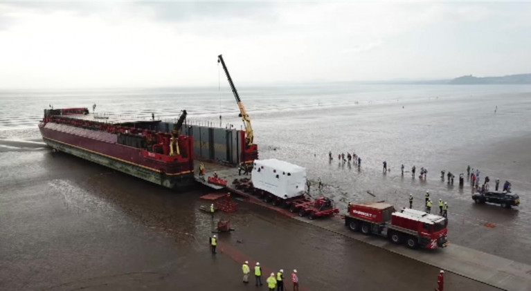 Takes some shifting.... as Afloat adds the transformer attracted crowds on a beach in north Wales from where it is to reach its final destination at Trawsfynyd tomorrow. In the distance is the  Llŷn Peninsula which juts into the Irish Sea south of Anglesey.