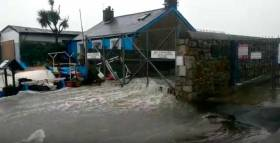 The scene at Bulloch Harbour where a storm surge caused waves to break over the harbour. Scroll down for video.