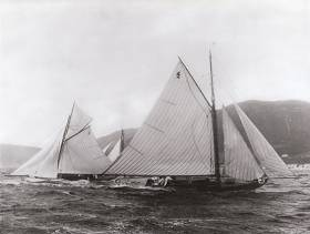 The newly-built Fife-designed Belfast Lough Class I 25ft LWL boats Feltie (George Clark) and Halcyone (Bertie Brown) in action in Clyde Fortnight 1897, just four weeks after they'd had their maiden race on May 29th at Carrickfergus, where they were built by John Hilditch. In a classic Firth of Clyde squall, Feltie is still hanging on to her topsail, though Halcyone under her lowers seems to be providing her robust helmsman with quite enough to be thinking about as he shapes up for a gybe. Belfast Lough Class I made such an impressive debut in Scotland in 1897 that a lengthy report of their success were carried in the New York Times. Photo: Courtesy RUYC