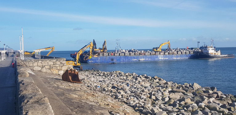 East Pier, Dun Laoghaire Harbour where contractors using heavy machinery on board a barge with tug Vanguard on station just offshore in Scotsman's Bay last month. Since then granite rocks continue to be placed in position shoring up previous damage caused by Storm Emma in 2018.
