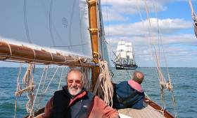 Hal Sisk aboard the newly-restored 1894-built Peggy Bawn in Dublin Bay in 2005, with the square-rigger Jeanie Johnston in the background. Peggy Bawn will be one of the stars of the Classics & Traditional section in the Volvo Dun Laoghaire Regatta 2017, celebrating the Bicentenary of the harbour. Photo: W M Nixon