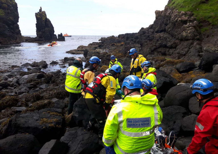 Coastguard and lifeboat volunteers stretcher the casualty from the cave in Smuggler's Cove on Friday 7 August