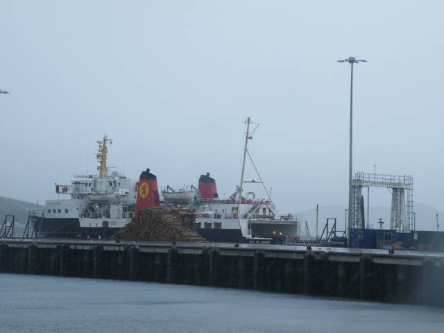 CalMac's Ardrossan-Campbeltown ferry, M.V. Isle of Arran at the Mull of Kintyre port in June. On the New Quay are stacked round timber (logs) for export by cargoship. The berth in the foreground is currently occupied by 5-star cruise tallship, Sea Cloud II having called yesterday to Dublin and tomorrow, Belfast.