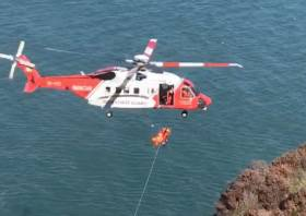 Rescue 116 winches the casualty to safety from the cliff base at Balscadden