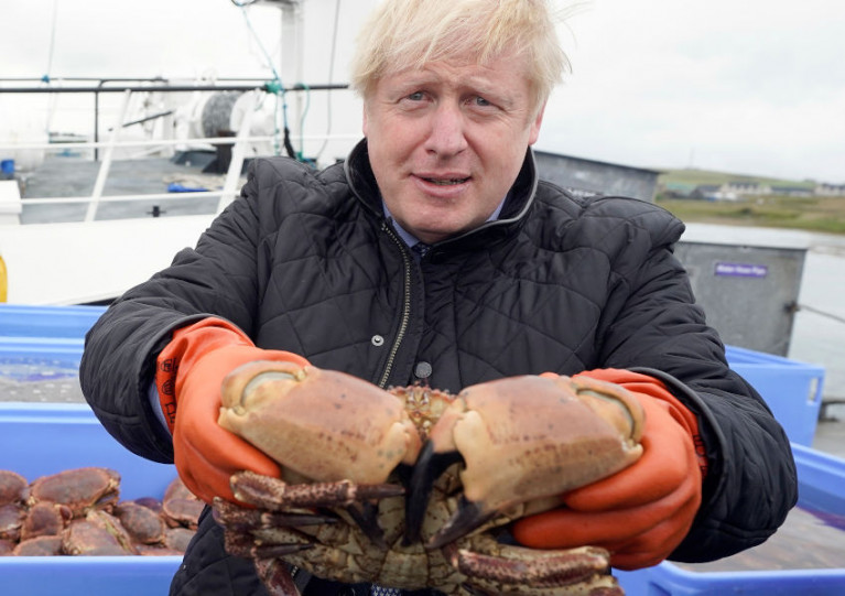 UK Prime Minister Boris Johnson comes to grips with live crab in Orkney this past July